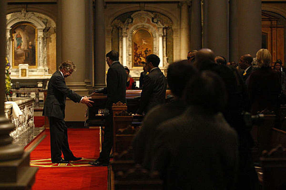 Mourners stand as the casket is moved to the front of St. Ignatius Church for the funeral service of Burl Toler in San Francisco, Calif. on Wednesday, August 26, 2009.