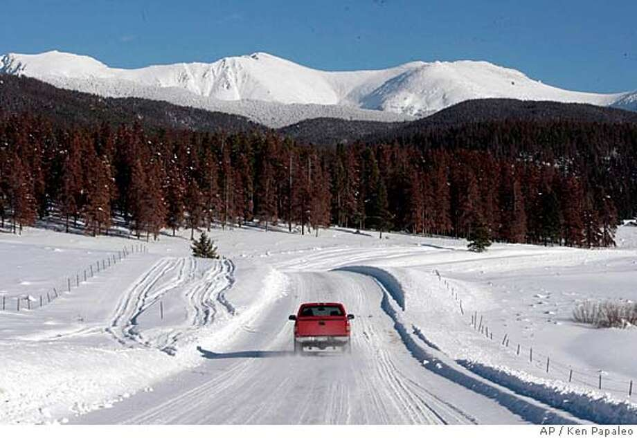 A pickup truck makes its way down a snow-covered road near Fraser, Colo., on Jan. 14, 2008. The American West started heating up five years ago, Colorado started losing its lodgepole pine forests to a beetle infestation. (AP Photo/Rocky Mountain News, Ken Papaleo) **MANDATORY CREDIT** **TV OUT , MAGS OUT, **DENVER OUT** Photo: Ken Papaleo
