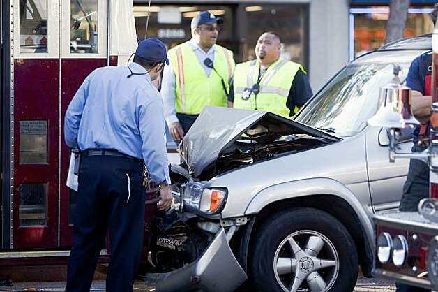 Muni employees inspect the scene of accident between an SUV and two outbound historic F-line trains on Market Street in San Francisco on Monday. Photo: Stephen Lam, The Chronicle