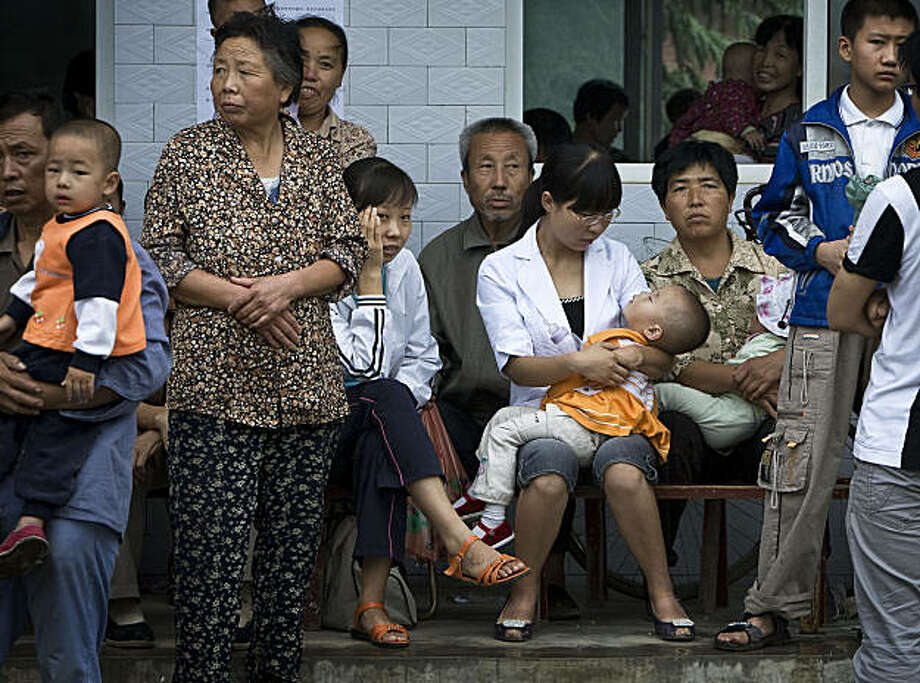 In this photo taken on Tuesday, Aug. 18, 2009, villagers wait with their children for blood tests at a school after the Dongling Lead and Zinc Smelting Co. smelting plant poisoned hundreds of children in Fengxiang county, Shaanxi province, China. More than 1,300 children have been sickened by lead poisoning in Hunan province, the second such case involving a large number of children this month, state media said Thursday. (AP Photo/Andy Wong) Photo: Andy Wong, AP