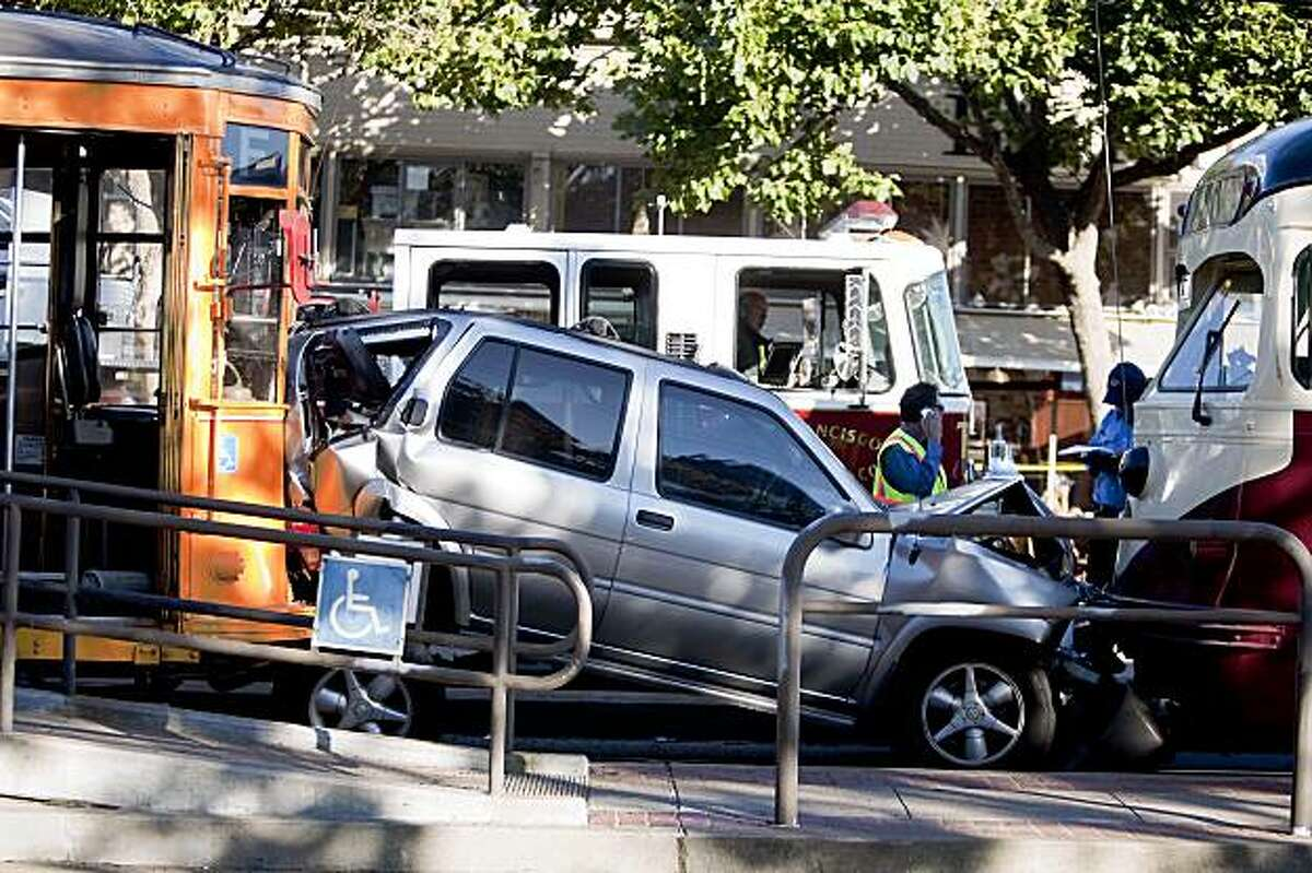 Emergency personnel inspects the scene of accident between a SUV and two outbound historic F-train on Market Street and Noe Street in San Francisco, Calif. on Monday, Aug. 3, 2009.