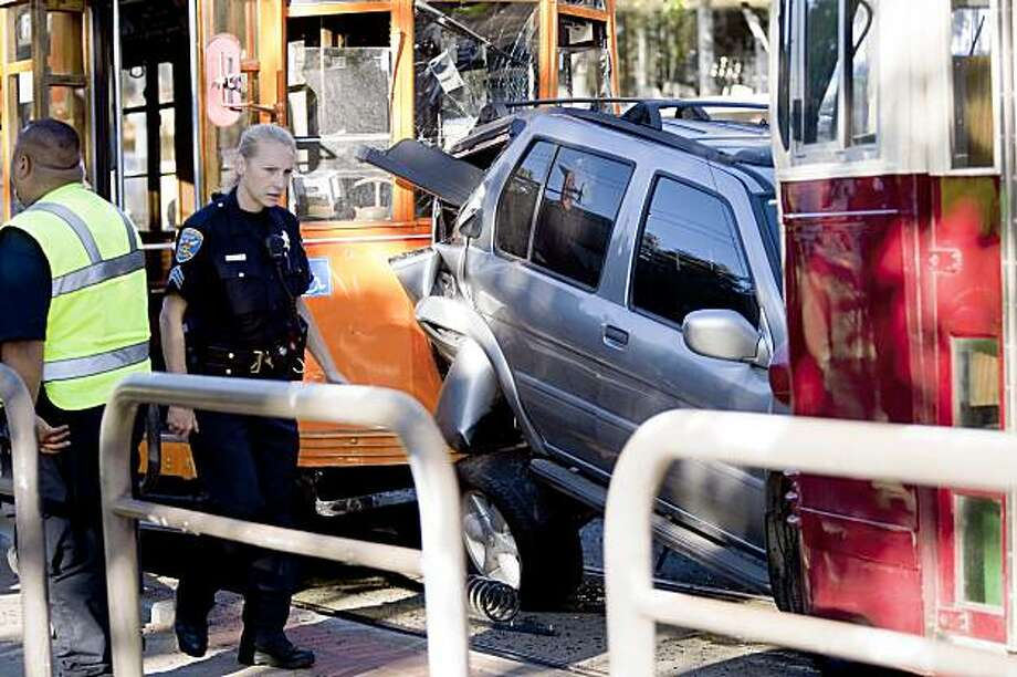 Emergency personnel inspects the scene of accident between a SUV and two outbound historic F-train on Market Street and Noe Street in San Francisco, Calif. on Monday, Aug. 3, 2009. Photo: Stephen Lam, The Chronicle