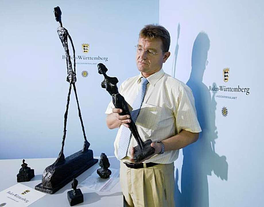 A police press officer presents imitation sculptures by Swiss artist Alberto Giacometti in the southern German city of Stuttgart on August 19, 2009. The police found a warehouse with many thousand fake sculptures by the Swiss artist. AFP PHOTO DDP / MICHAEL LATZ   GERMANY OUT (Photo credit should read MICHAEL LATZ/AFP/Getty Images) Photo: Michael Latz, AFP/Getty Images