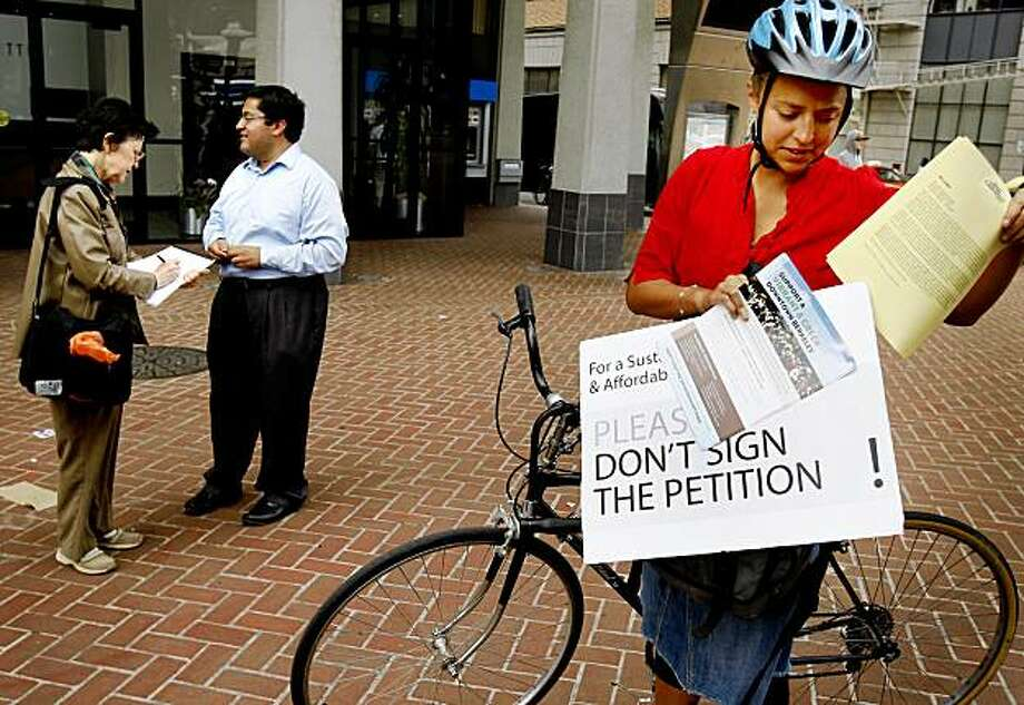 Savlan Hauser (right) readied her anti-petition literature as Berkeley City Councilman Jesse Arreguin (center) got resident Therese Pipe to sign the controversial petition. Virtually all of Berkeley's elected officials are urging citizens not to sign a petition dealing with developing the downtown area. Photo: Brant Ward, The Chronicle