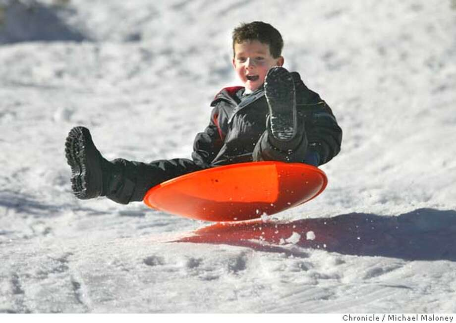 OUTDOORS236.JPG  Jordan Schabacker (6 years old) of American Canyon slides down an icy slope at Echo Summit Sno-Park near lake Tahoe.  Photos of winter/snow activities for the Outdoors Quarterly.  Event on 12/1/03 in Sierras.  MICHAEL MALONEY / The Chronicle Photo: MICHAEL MALONEY