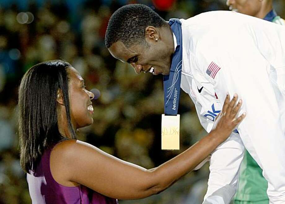 United States' Dwight Phillips, right, receives his gold medal from Jesse Owens' granddaughter Marlene Dortch, left, during the medal ceremony for the Men's Long Jump at the World Athletics Championships in Berlin on Saturday, Aug. 22, 2009. (AP Photo/Markus Schreiber) Photo: Markus Schreiber, AP