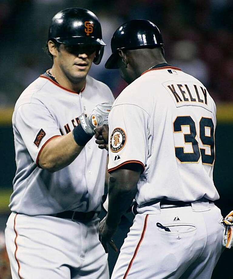 San Francisco Giants' Ryan Garko, left, gets congratulated by first base coach Roberto Kelly after Garko hit  a two run double off Cincinnati Reds pitcher Francisco Cordero during the tenth inning of a baseball game, Tuesday, Aug. 18, 2009 in Cincinnati.  The Giants won 8-5.  (AP Photo/Tony Tribble) Photo: Tony Tribble, AP