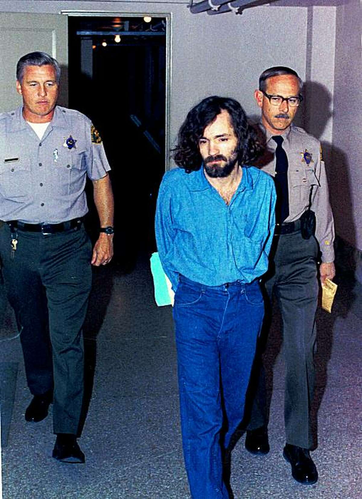 Charles Manson, head of the cult the Manson Family being escorted by deputy sheriffs on his way to court, in Los Angeles, Calif., after being charged with murder-conspiracy in the Tate-LaBianca slayings Aug. 20, 1970.