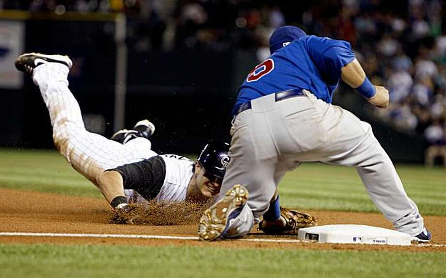 Colorado Rockies' Troy Tulowitzki, left, slides safely into third base with a triple as Chicago Cubs third baseman Jake Fox fields the throw in the seventh inning of a baseball game in Denver on Monday, Aug. 10, 2009. (AP Photo/David Zalubowski) Photo: David Zalubowski, AP