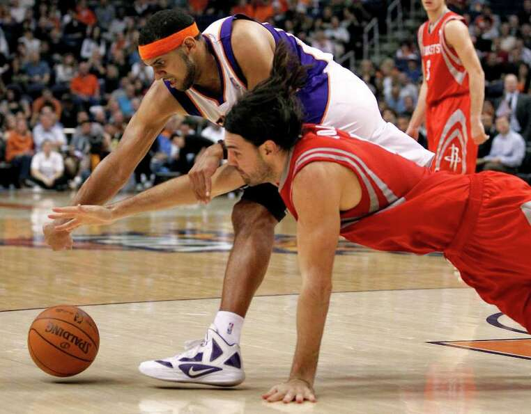 Houston Rockets  forward Luis Scola, bottom, of Argentina, battles Phoenix Suns Jared Dudley for a l