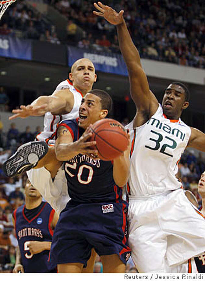 St Mary's Diamon Simpson (C) shoots between Miami's Jimmy Graham (L) and Brian Asbury during the first half of their first round NCAA men's basketball tournament game in Little Rock, Arkansas, March 21, 2008. REUTERS/Jessica Rinaldi (UNITED STATES) Photo: JESSICA RINALDI