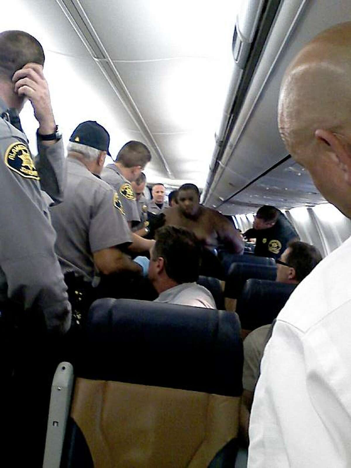 This picture shot by a passenger aboard Southwest Airlines Flight 947 shows Alameda County Sheriff's deputies arresting a man who allegedly exposed himself to his female seat-mate, punched her when she screamed, and then stripped off all of his clothes as flight attendants and other passengers tried to subdue him.