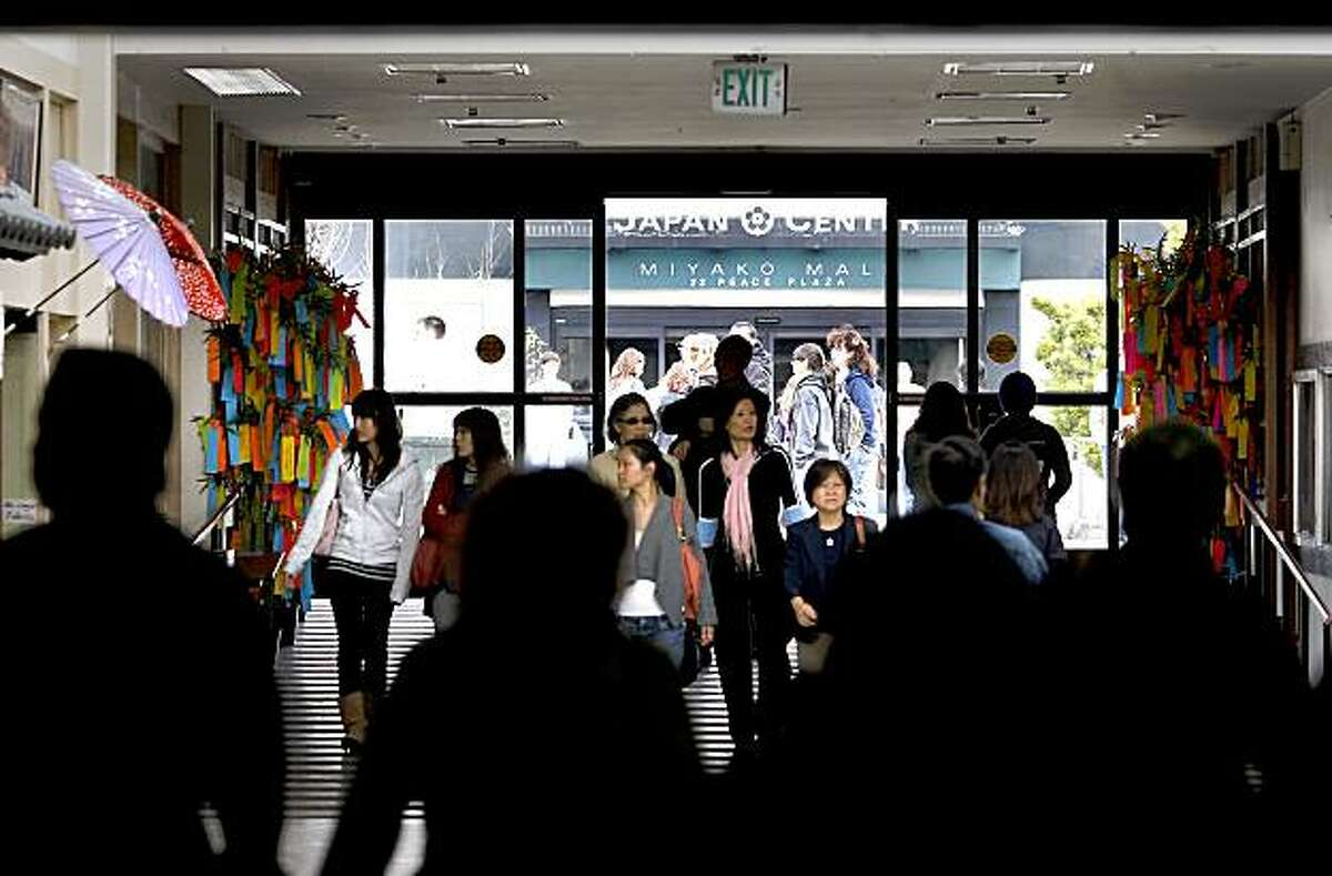 People walk through the huge glass doors of Japantown's Kintetsu Mall just west of the Peace Pagoda.