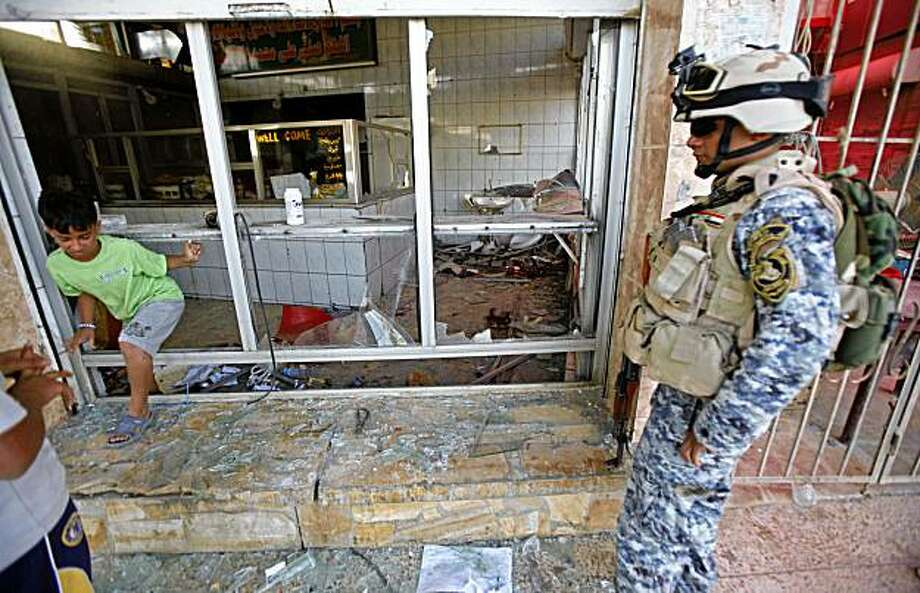 A policeman inspects a damaged restaurant in Baghdad, Iraq, Monday, Aug. 17, 2009. Two bombs hidden in a plastic bags near a falafel stand exploded simultaneously shortly on Sunday, killing four people and wounding 25 others, Iraqi officials said. Photo: Hadi Mizban, AP