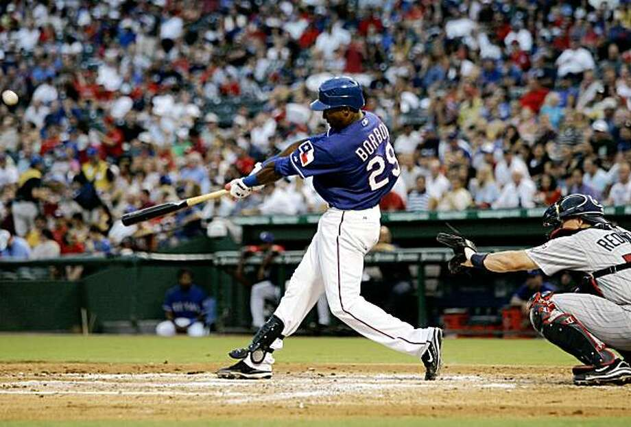 Minnesota Twins catcher Mike Redmond, right, looks on as Texas Rangers' Julio Borbon connects for his first major league home run off a pitch from the Twins' Anthony Swarzak in the third inning of a baseball game, Thursday, Aug. 20, 2009 in Arlington, Texas.   (AP Photo/Tony Gutierrez) Photo: Tony Gutierrez, AP
