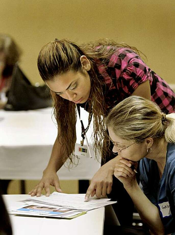 Kohl's associate Maria Enriquez (left) helped job applicant Galina with a question. Kohl's held a job fair in Millbrae at the Hyatt Regency near the San Francisco Airport this weekend and is expected to attract thousands of out-of-work hopefuls. Photo: Brant Ward, The Chronicle
