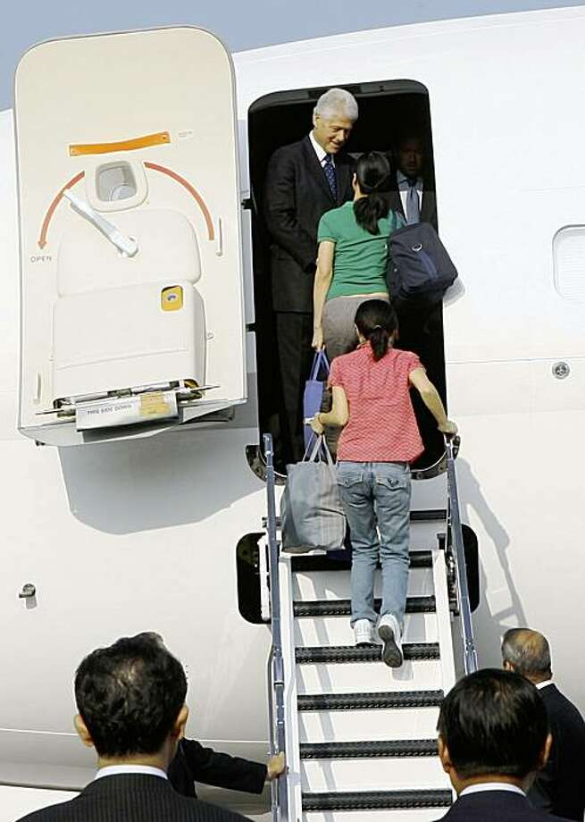 In this photo released by China's Xinhua News Agency, the two female American journalists, in green and red shirts, just amnestied by North Korea go aboard a chartered plane carrying the homebound former President Bill Clinton, top, to leave Pyongyang, North Korea, Wednesday, Aug. 5, 2009. His mission accomplished, former President Bill Clinton left Pyongyang early Wednesday accompanied by American journalists Euna Lee and Laura Ling after North Korean leader Kim Jong Il pardoned the women from their 12-year prison sentences. (AP Photo/Xinhua, Zhang Binyang) ** NO SALES ** Photo: Zhang Binyang, AP