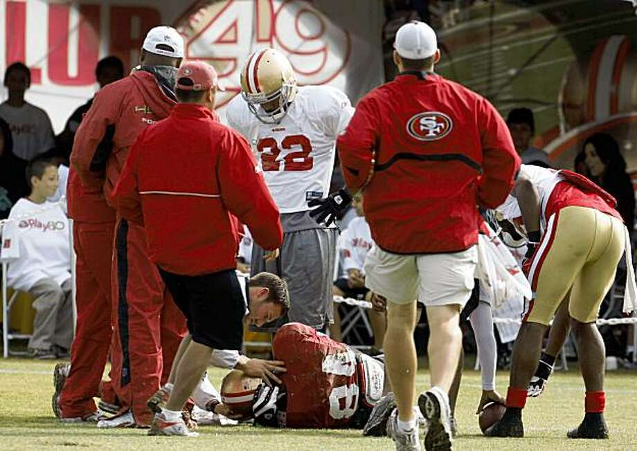 49ers wide receiver Josh Morgan (84) lies on the field as teammates and trainers tend to him after he was injured making a spectacular catch during thier summer camp workout in Santa Clara, Calif., on August 6,  2009. Photo: Frederic Larson, The Chronicle