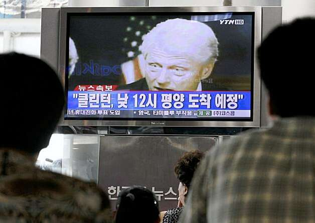 "South Koreans watch a TV broadcasting news about former President Bill Clinton is heading to North Korea at the Seoul Railway Station in Seoul, South Korea, Tuesday, Aug. 4, 2009. Clinton made a surprise trip to North Korea on Tuesday amid an international standoff over the country's nuclear program and concerns about two U.S. reporters imprisoned in Pyongyang since March. The letters read ""Alert, Clinton will arrive at Pyongyang around 12:00."" (AP Photo/Ahn Young-joon) Photo: Ahn Young-joon, AP"
