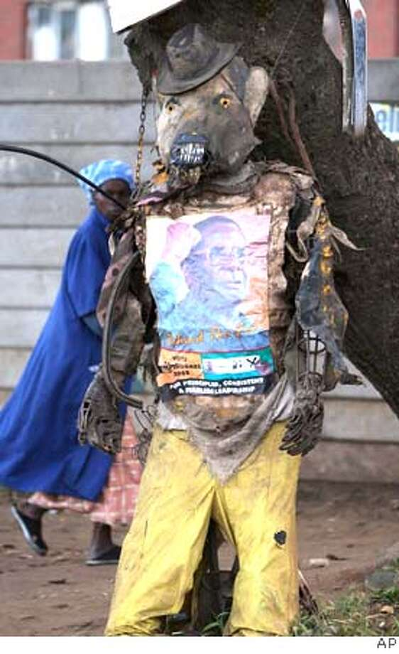 An election poster of Zimbabwe's President Robert Mugabe, is pinned in an effigy mocking his government in Harare, Wednesday April 2, 2008. The main opposition party has claimed outright victory for its leader Morgan Tsvangirai, saying he had won 50.3 percent of the vote compared to 43.8 percent for Mugabe. President Robert Mugabe's party lost control of parliament, the latest official results showed Wednesday, hours after the opposition claimed it also won the presidency. The Zimbabwe Electoral Commission results appear to confirm the unraveling of a regime that has ruled this southern African country since independence from Britain three decades ago, in recent years overseeing the collapse of the economy and accused of stifling democracy. (AP Photo) Photo: AP