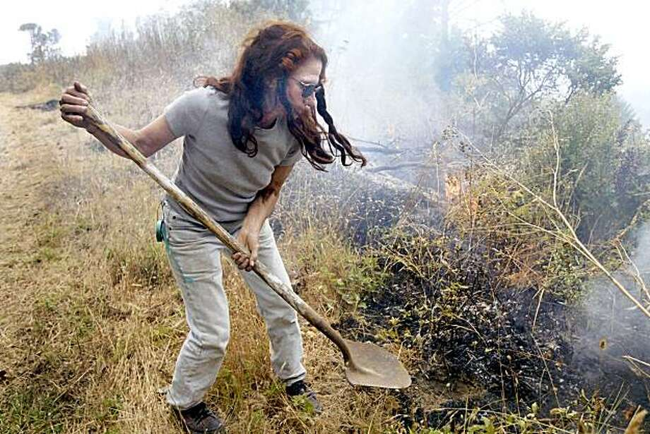 Swanton area resident Valerie Corral tries to snuff out a hot spot along a road near her property as part of the battle against the Lockheed  fire Saturday Aug. 15, 2009 north of Santa Cruz, Calif.  (AP Photo/Santa Cruz Sentinel, Bill Lovejoy) Photo: Bill Lovejoy, AP
