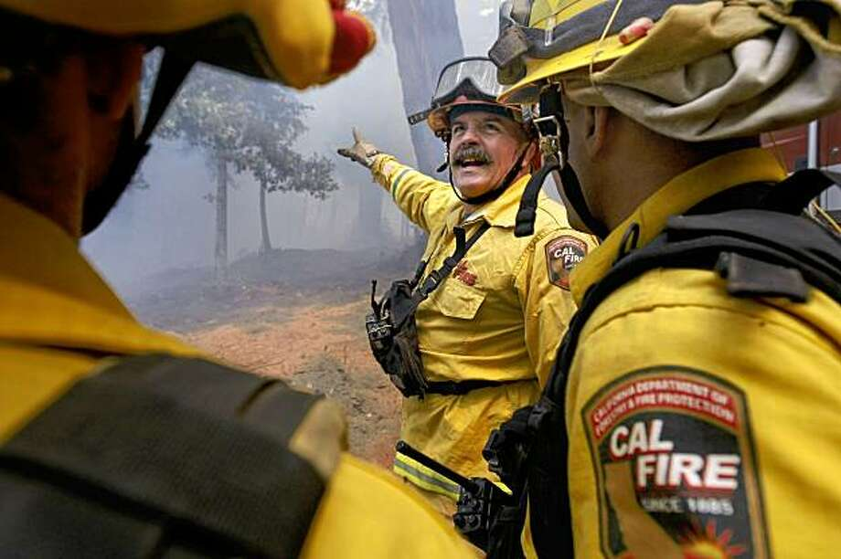 Fire Captain Bill Finch directs firefighters along Warnella Road. Photo: Michael Macor, The Chronicle