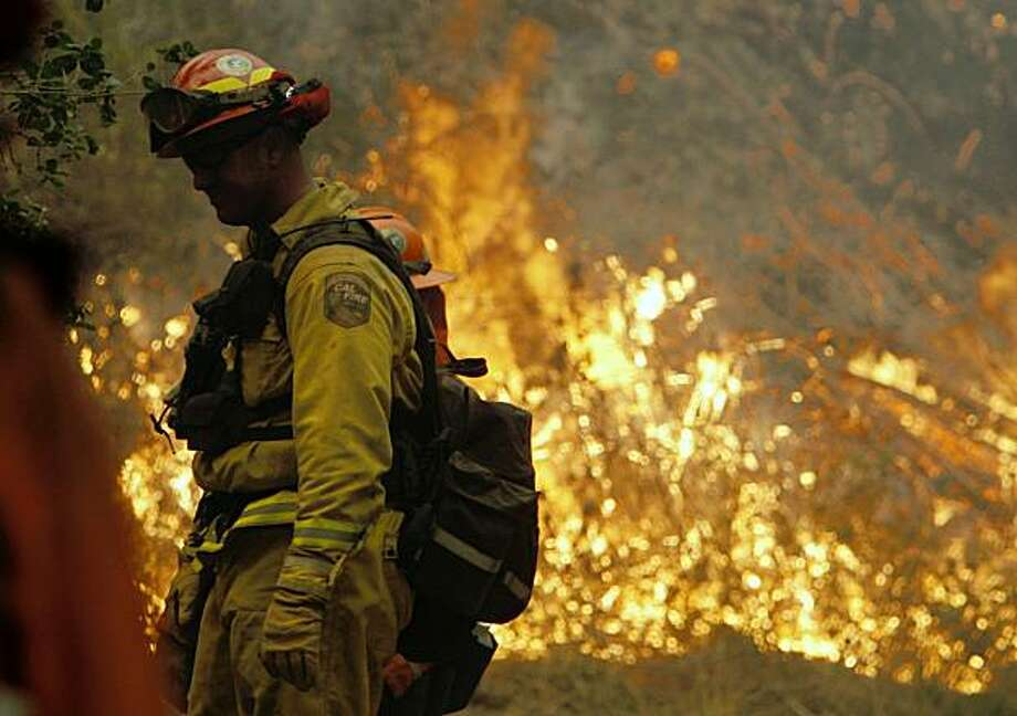 Aaron Latta from Cal Fire tends to the Lockheed Fire as it moves toward homes as it burns along a steep area of timber and heavy brush by Big Creek Ranch off Swanton Road. Photo: Frederic Larson, The Chronicle