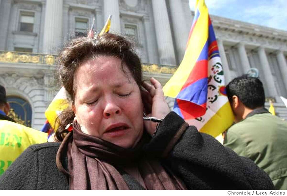 ###Live Caption:Bonnie McCalla cries outside San Francisco City Hall, Tuesday April 1, 2008, at a rally protesting the presence of the Olympic torch in San Francisco, Calif.