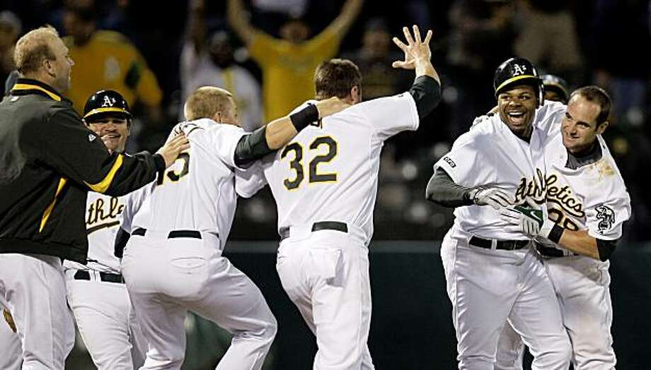 Oakland Athletics' Rajai Davis, second from right, celebrates with teammates, including Adam Kennedy, right, and Jack Cust (32) after Davis made the game-winning hit against the Texas Rangers in the ninth inning of a baseball game Monday, Aug. 3, 2009, in Oakland, Calif. Oakland won 3-2.  (AP Photo/Ben Margot) Photo: Ben Margot, AP