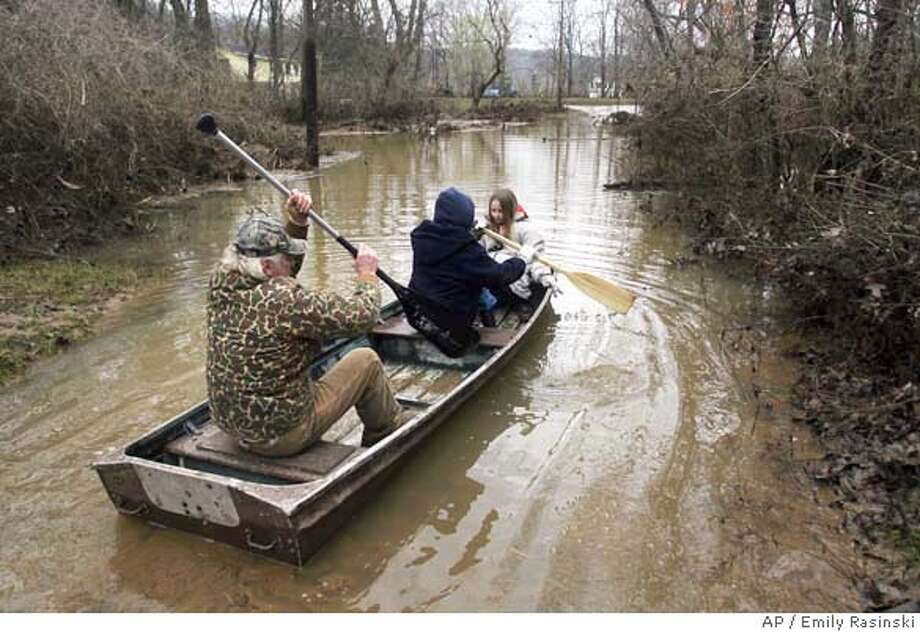 ###Live Caption:Dan Yates paddles his neighbors Kathy Lamkemeyer and her daughter Natalie, 9, down Beach Drive so they can look at the damage to their home caused by the flooding of the Big River in Jefferson County, Mo., Sunday, March 23, 2008. (AP Photo/St. Louis Post-Dispatch, Emily Rasinski) ** MAGS OUT, NO SALES, TV OUT, NO ARCHIVES **###Caption History:Dan Yates paddles his neighbors Kathy Lamkemeyer and her daughter Natalie, 9, down Beach Drive so they can look at the damage to their home caused by the flooding of the Big River in Jefferson County, Mo., Sunday, March 23, 2008. (AP Photo/St. Louis Post-Dispatch, Emily Rasinski) ** MAGS OUT, NO SALES, TV OUT, NO ARCHIVES **###Notes:###Special Instructions:MAGS OUT, NO SALES, TV OUT, NO ARCHIVES Photo: Emily Rasinski
