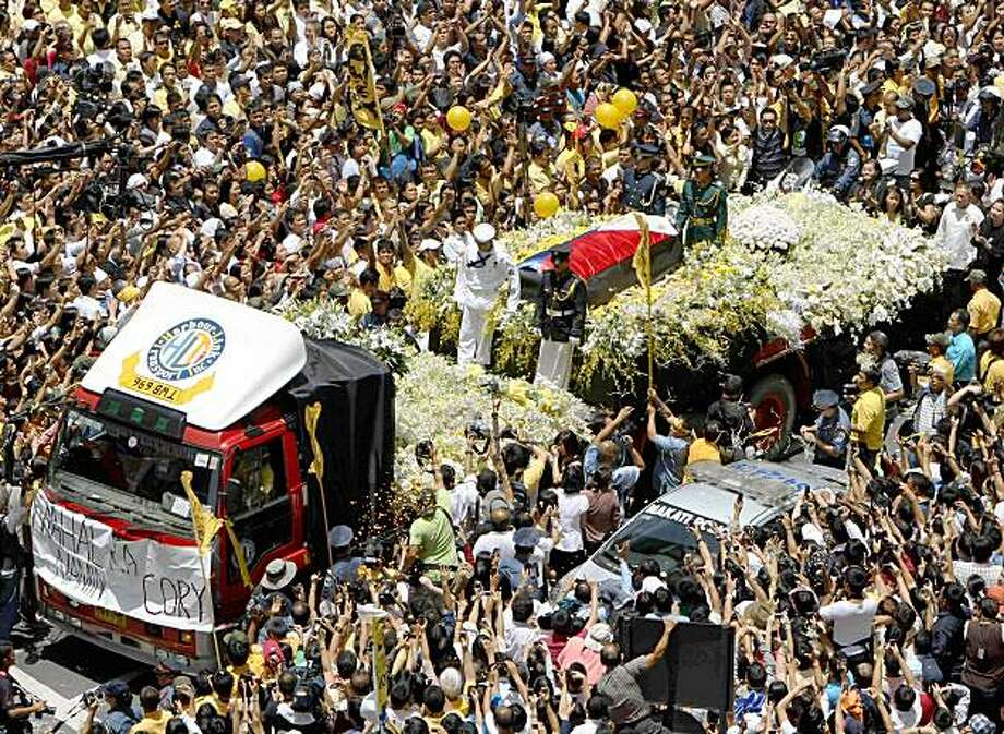 "Tens of thousands of supporters gather at the funeral motorcade for former Philippine President Corazon Aquino as it inches its way along Manila's financial district of Makati city on the way to the Manila Cathedral Monday Aug. 3, 2009 in Manila, Philippines. Masses of mourners yelled her name as former President Corazon Aquino's body was escorted Monday through streets in Manila and along  a historic avenue that 23 years ago became the site of a ""people power"" revolt against a dictator. (AP Photo) Photo: AP"