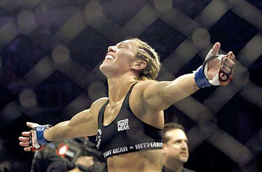 "Cris ""Cyborg"" Santos, of Brazil, celebrates after beating Gina Carano in a Strikeforce mixed martial arts Female Middleweight Championship match on Saturday, Aug. 15, 2009, in San Jose, Calif. Santos won by TKO in the first round to win the championship. (AP Photo/Jeff Chiu) Photo: Jeff Chiu, AP"