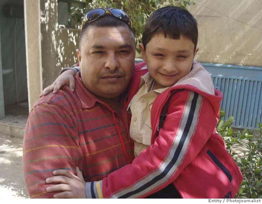 Firas holds his nine-year-old son Mustafa Wednesday, March 5, 2008 in Baghdad. Mustafa was shot at a U.S. checkpoint while riding in the back of his family's car last August. Hiis father drove toward the checkpoint, confused by the American soldiers' commands that he should halt, but the boy's life was saved by a surgery paid for through an American government program mandated by Congress to give relief to innocent victims of U.S. military action. (AP Photo/Bradley Brooks) Photo: Bradley Brooks