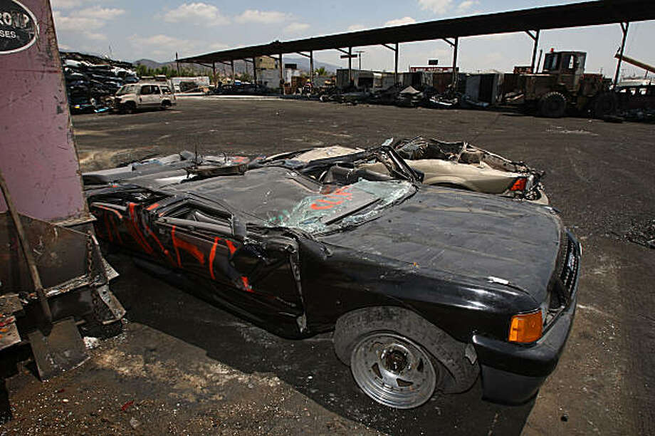 SUN VALLEY, CA - AUGUST 7: A crushed Isuzu Rodeo, that was turned in through the Cash for Clunkers federal program, lies near a car crusher at the Aadlen Brothers Auto Wrecking junkyard on August 7, 2009 in Sun Valley, California. The Senate voted 60 to 37 for the approval of an additional $2 billion funding for the popular auto rebate initiative that offers consumers $3,500 to $4,500 to trade in their older high-mileage vehicle for a more fuel-efficient one. The additional funding means that another half million vehicles can be purchased, providing an increased boost to the sluggish auto industry. The program had created such a demand that some locales are reporting shortages of popular high-mileage models like the Ford Focus and Toyota Prius. Under the program, dealers are instructed to replace the oil of the trade-ins with a solution of sodium-silicate and water and run the engine until it is damaged beyond repair. Critics charge that auto parts recyclers and charities that rely on old car donations are being hurt by the policy. (Photo by David McNew/Getty Images) Photo: David McNew, Getty Images