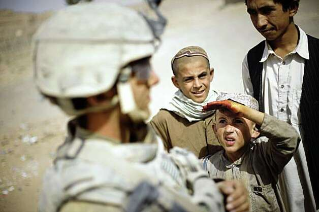 Afghan children are seen next to a soldier from the 5th Striker Brigades, as he stands guard on a road in a village on the outskirts of Spin Boldak, about 100 kilometers (63 miles) southeast of Kandahar, Afghanistan,Thursday, Aug. 6, 2009. Thousands of U.S. troops are deploying in southern Afghanistan as part of an effort to prevent the Taliban from disrupting the country's Aug. 20 presidential ballot.  (AP Photo/Emilio Morenatti) Photo: EMILIO MORENATTI, AP