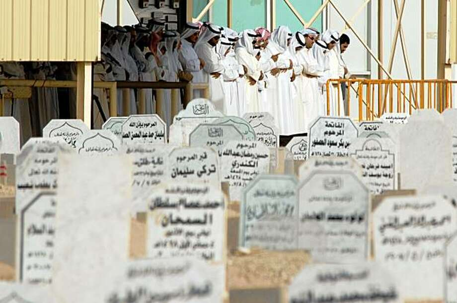 Kuwaiti men pray over the remains of some of the 41 women and children who died in a fire in a wedding tent Saturday, before burying them at Sulaybikhat Cemetery in Kuwait Sunday  Aug . 16  2009. The fire  consumed the structure in a blazing inferno lasting just three minutes, the fire department chief said Sunday. (AP Photo/ Nasser Wajeeh) Photo: Nasser Wajeeh, AP