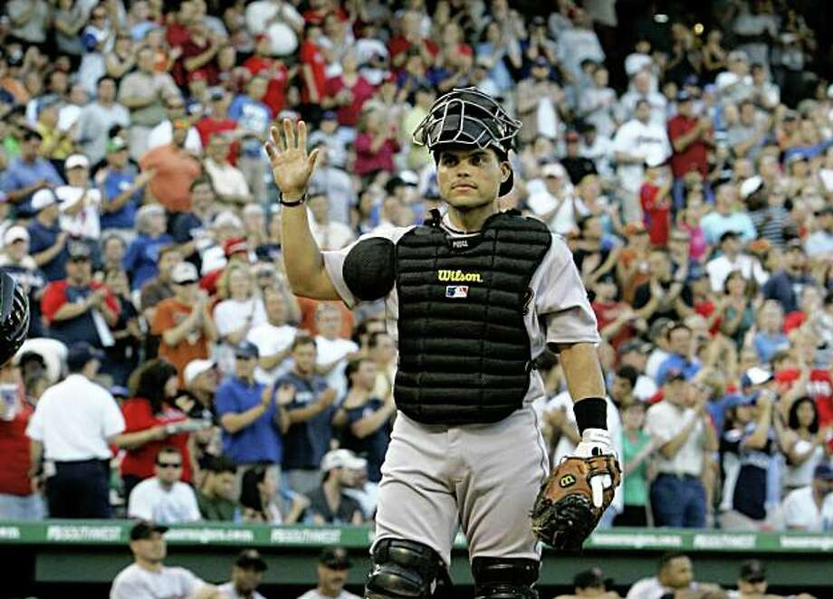 Houston Astros catcher Ivan Rodriguez acknowledges cheers from fans after a video tribute was played during the third inning of a baseball game against the Texas Rangers in Arlington, Texas, Wednesday, June 17, 2009. Rodriguez passed Carlton Fisk for the major league record for games played by a catcher. (AP Photo/Tony Gutierrez) Photo: Tony Gutierrez, AP