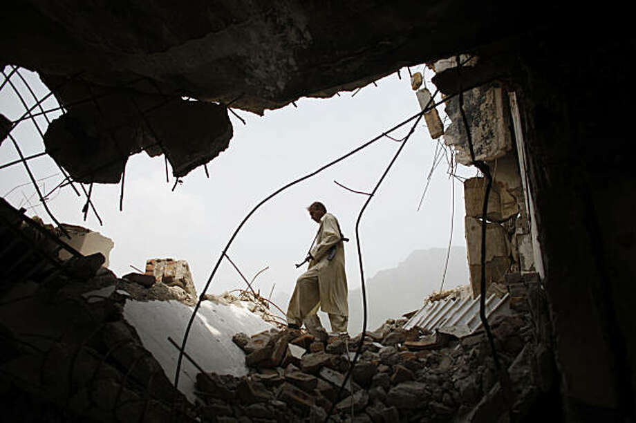 In this photo taken Friday, Aug. 14, 2009, member of a Lashkar, or local citizens' militia formed to fight against Taliban militants, walks through debris in Sultanwas village, Buner district, Pakistan, Friday, Aug. 14, 2009. A suicide bomber rammed an explosives-laden car into a checkpoint in Pakistan's northwestern Swat Valley, killing at least five people Saturday in a reminder that extremists can still strike despite the military's retaking of the area, police said. (AP Photo/Alexandre Meneghini) Photo: Alexandre Meneghini, AP