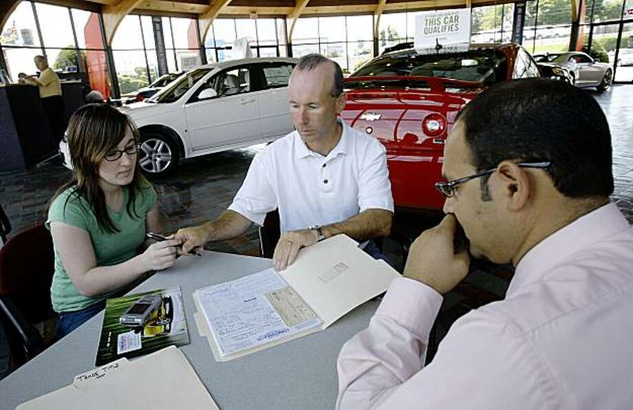 "Rick Mahoney of Billerica, Mass., center, passes a pen to his daughter Ally, left, as they sign the purchase contract in front of salesman Ivan Lovera, Tuesday, July 28, 2009, at Commonwealth Motors in Lawrence, Mass. The Mahoneys traded in their 1999 Chevrolet Tahoe for a new Chevrolet Aveo, taking advantage of the federal government's ""Car Allowance Rebate System,"" or ""CARS"" incentive program. (AP Photo/Charles Krupa) Photo: Charles Krupa, AP"