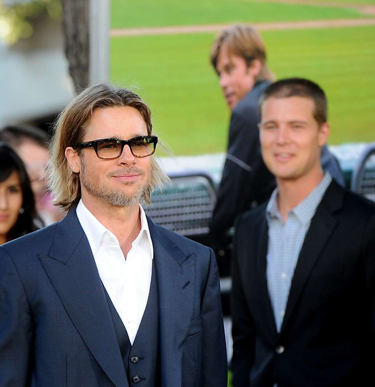 """Brad Pitt arrives for the world premiere of """"Moneyball"""" at the Paramount Theatre on Monday, Sept. 19, 2011, in Oakland, Calif. Behind him is doppleganger Reed Thompson who plays the young version of Brad's character, Billy Beane, in the movie."""