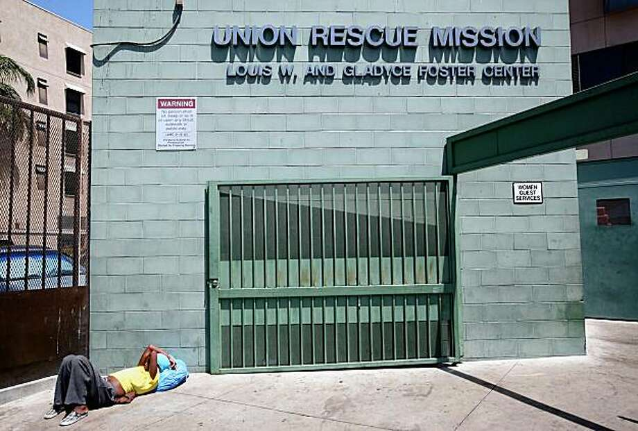 In this Thursday, July 23, 2009 picture, a homeless woman rests at the back entrance of the woman's section of the Union Rescue Mission in downtown Los Angeles. The majority of a $1.6 million settlement negotiated after a hospital was accused of dumping 150 mentally ill patients on Skid Row hasn't gone to charities working with the city's homeless. (AP Photo/Richard Vogel) Photo: Richard Vogel, AP