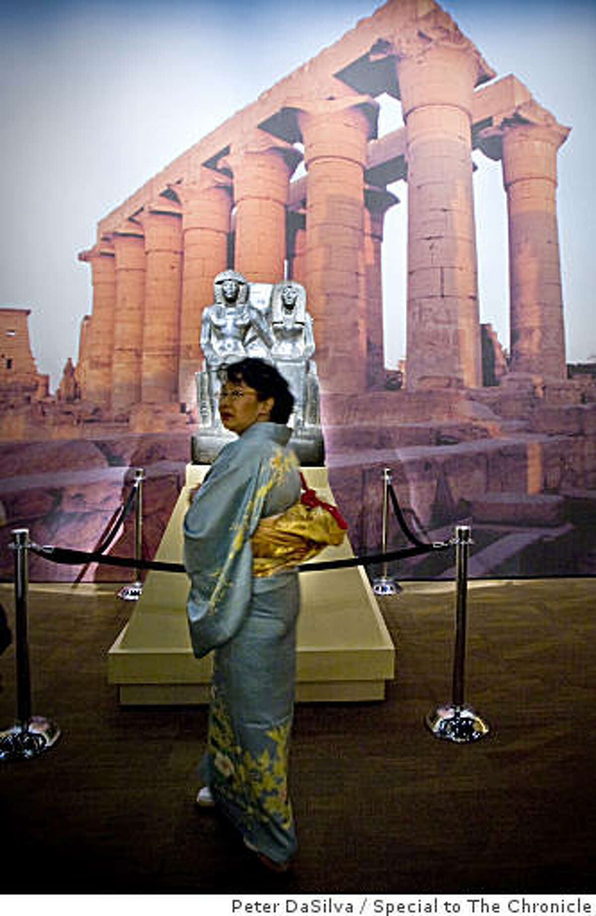 """Guest Dr. Sachiko Nishimura of the Tutankhamun and the Golden Age of the Pharaohs opening gala, glances off after looking at the """"Statue of Tuthmosis IV and His Mother, Tiaa"""" in the Tutankhamun exhibit at the de Young Museum in San Francisco, California on Jun. 23, 2009."""