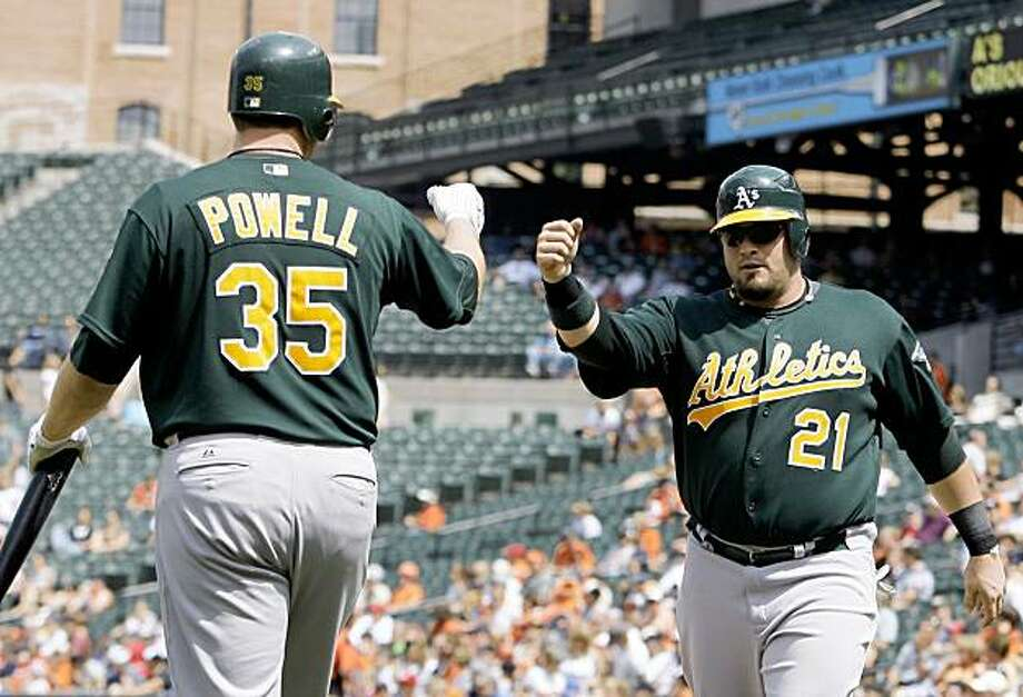 Oakland Athletics' Tommy Everidge (21) celebrates with teammate Landon Powell (35) after scoring on a sacrifice fly during the fourth inning of a baseball game against the Baltimore Orioles, Wednesday, Aug. 12, 2009, in Baltimore. The Athletics won 6-3. (AP Photo/Rob Carr) Photo: Rob Carr, AP