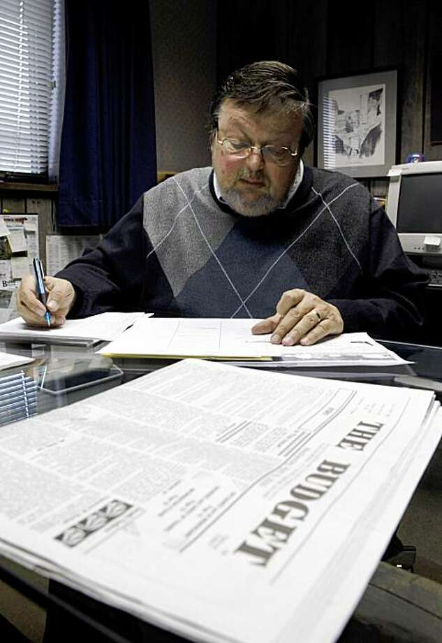 In this April 15, 2009 photo, The Budget publisher Keith Rathbun is shown in his office in Sugarcreek, Ohio, as he works on the weekly Amish newspaper. Nearly 20,000 people across the U.S. and Canada subscribe to The Budget, a 119-year-old publication that remains the dominant means of communication among the Amish, a Christian denomination with about 227,000 members nationwide who shun cars for horse-drawn buggies and avoid hooking up to the electrical grid. (AP Photo/Kiichiro Sato) Photo: Kiichiro Sato, AP