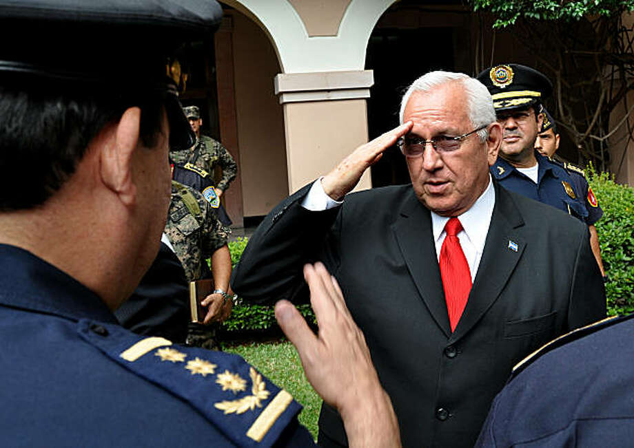 Honduran de facto President Roberto Micheletti (R) salutes National Police directors after a meeting at the presidential palace on July 28, 2009 in Tegucigalpa. The United States on Tuesday upped pressure on the interim leaders of Honduras, as ousted President Manuel Zelaya remained defiant in Nicaragua one month after the army sent him away.   AFP PHOTO/Yuri Cortez (Photo credit should read YURI CORTEZ/AFP/Getty Images) Photo: Yuri Cortez, AFP/Getty Images