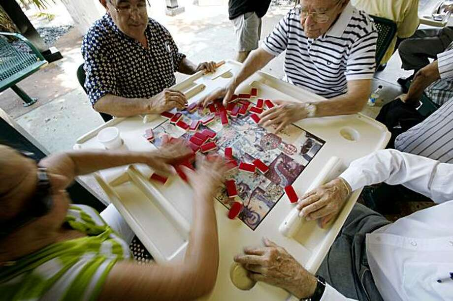 This Aug. 5, 2009 photo shows domino players at play shuffling dominos at Maximo Gomez Park, also known as Domino Park, in the Little Havana neighborhood of Miami. (AP Photo/Wilfredo Lee) Photo: Wilfredo Lee, AP