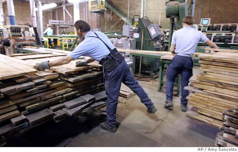 ** CORRECTS DATE TO THURSDAY, MARCH 27 ** Amishmen feed wood into a planer at the Sheoga Hardwood Flooring & Paneling company in Middlefield, Ohio on Thursday, March 27, 2008. Sheoga converted 3.7 million board feet of lumber into hardwood flooring in 2007. The Commerce Department reported Thursday that gross domestic product increased at a feeble 0.6 percent annual rate in the October-to-December quarter. (AP Photo/Amy Sancetta) Photo: Amy Sancetta