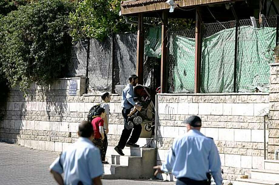 Israeli policemen stand guard as Jewish settlers enter a Palestinian house following the eviction of the family that used to live in it in occupied east Jerusalem's Arab district of Sheikh Jarrah on August 2, 2009. Israeli policemen wielding clubs kicked out two Palestinian families from their homes in the sensitive neighbourhood, defying international protests over Jewish settlement activity in the area. An Israeli court had ordered the eviction of the 53 Palestinians, including 19 minors, following an appeal by the Nahalat Shimon International settler group which claimed Jewish settlers have title deeds for the properties, despite UN and Palestinian denials. AFP PHOTO /AHMAD GHARABLI (Photo credit should read AHMAD GHARABLI/AFP/Getty Images) Photo: Ahmad Gharabli, AFP/Getty Images