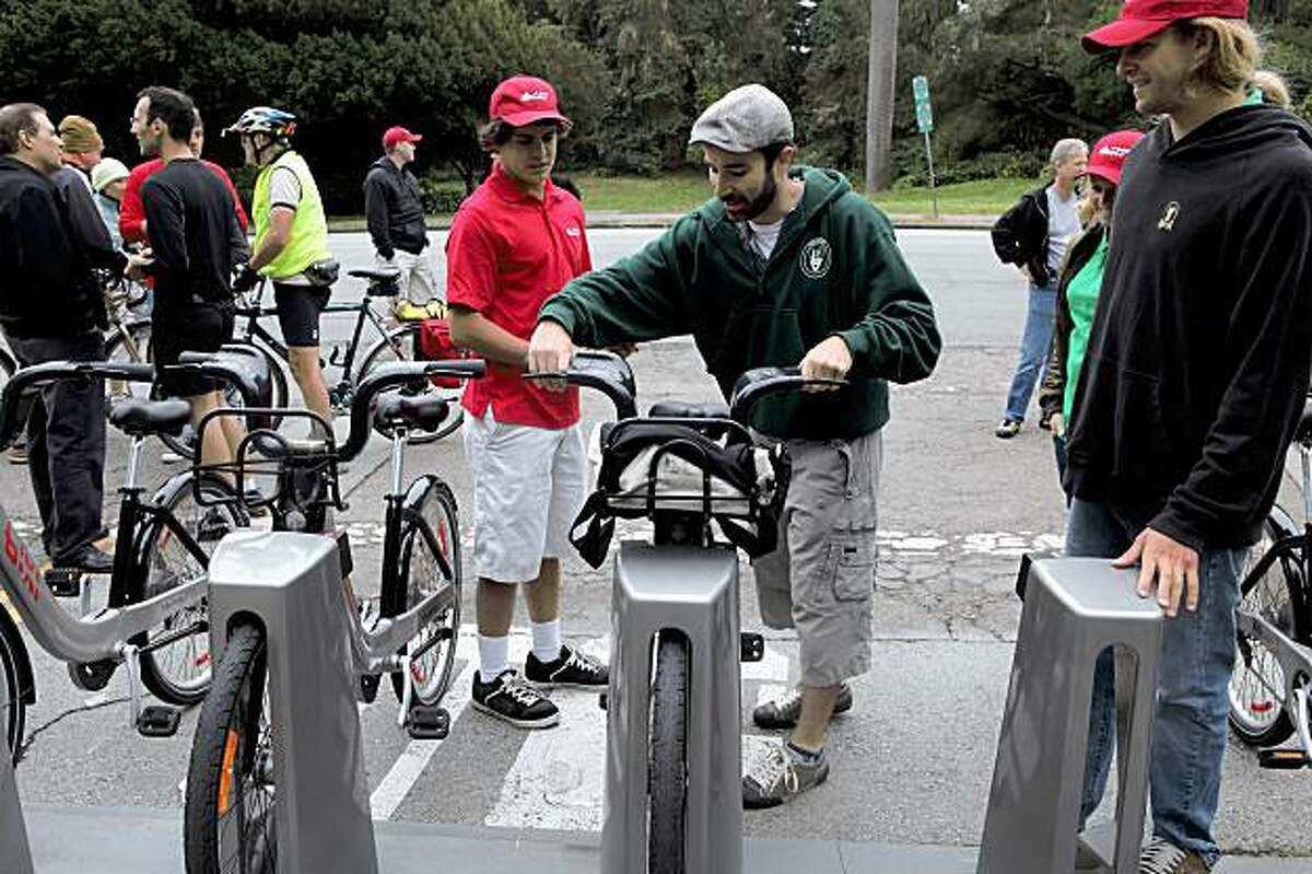 Dale Danley, of San Francisco, checks out a bike from Bixi, Montreal's bike sharing system, in Golden Gate Park in San Francisco, Calif, on Sunday, August 2, 2009. The program offers bike sharing for customers -- short-term bicycle rentals located throughout the city. Proponents say the results include reduced traffic congestion and vehicle emissions, and also less demand for parking.
