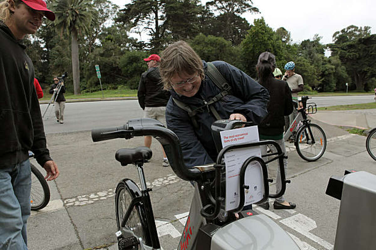 Laura Cleveland, of San Francisco checks out a bike from Bixi in Golden Gate Park in San Francisco, Calif, on Sunday, August 2, 2009. The program offers bike sharing for customers -- short-term bicycle rentals located throughout the city. Proponents say the results include reduced traffic congestion and vehicle emissions, and also less demand for parking.